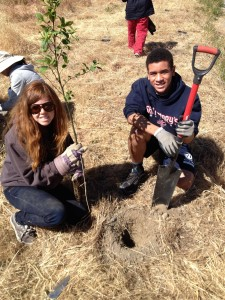Loic and Nina, two local high school students, work together to plant a tree.